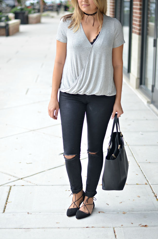 gray wrap tee with black lace bralette, black distressed skinny jeans, black bow choker, and black lace up flats | www.fizzandfrosting.com